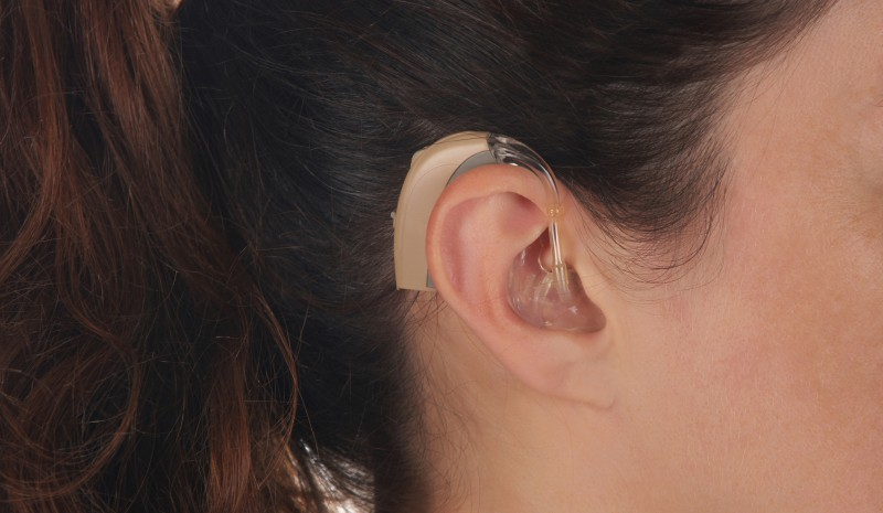 Beautiful young woman with Hearing Aid, closeup shot